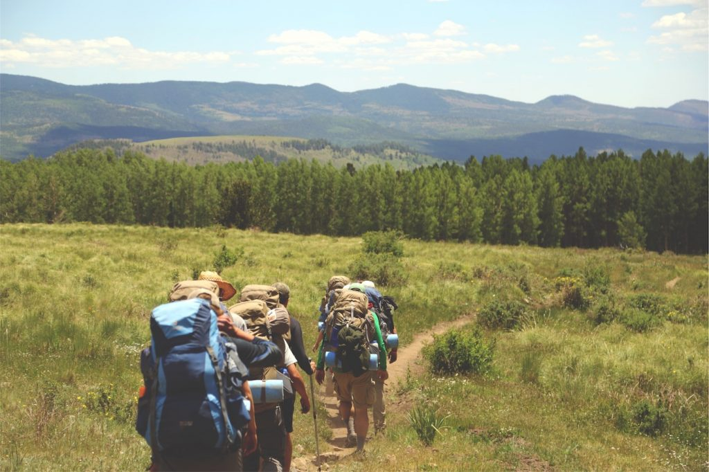 team of backpackers hiking in mountains