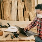 Man using a laptop at his wood working shop